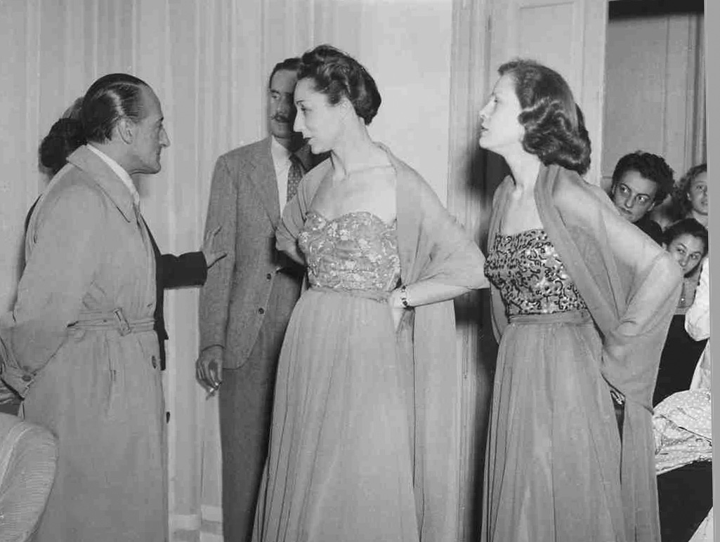 "Germana Marucelli shows some of her dresses to Totò (main italian XXth century comic actor) at her atelier during one of her ""Thursday Rendez-Vous"". One of the dresses is worn by Maria Cumani (centre), a ballet dancer, poetess and wife of Salvatore Quasimodo (poet and 1959 literature Nobel Prize laureate ) © Patellani 