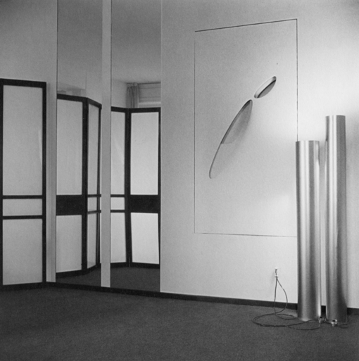 Partial view of Germana Marucelli's atelier in Corso Venezia 35, Milan, with a work by Paolo Scheggi (Intersuperficie curva bianca, 1964) fitted into the walls, and the aluminium lamps by Paolo Scheggi and Getulio Alviani, 1964. Photograph by Ada Ardessi ©  Isisuf, Milano | Archivio Germana Marucelli